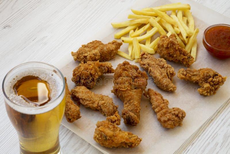 Snel voedsel: gebraden kippenbenen, kruidige vleugels, Frieten en kippenstroken met zuur-zoete saus en koud bier over witte houte royalty-vrije stock foto's