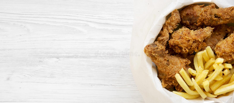 Snel voedsel: gebraden kippenbenen, kruidige vleugels, Frieten en tedere stroken in document vakje over witte houten achtergrond, royalty-vrije stock foto