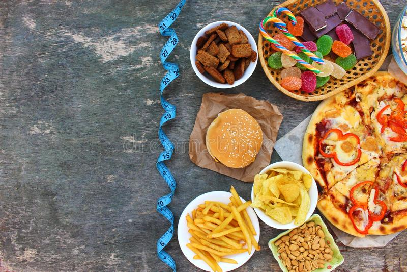 Snel voedsel, meetlint op oude houten achtergrond Concept troep het eten stock afbeelding