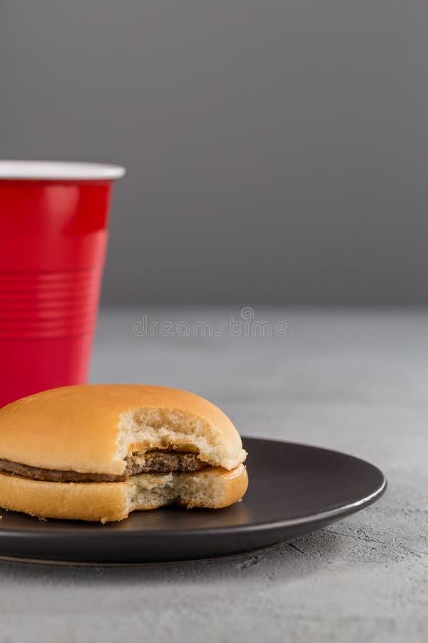 Snel voedsel met heerlijke gebeten hamburger op de achtergrond van een rode Kop met een drank royalty-vrije stock afbeeldingen