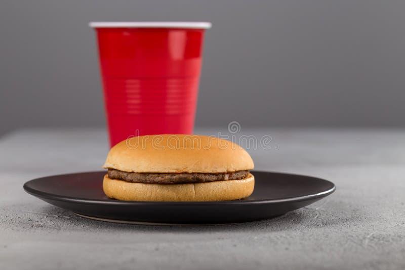 Snel voedsel met heerlijke hamburger op de achtergrond van een rode Kop met een drank royalty-vrije stock fotografie