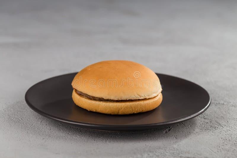 Snel voedsel met heerlijke hamburger op een zwarte ceramische plaat stock afbeelding