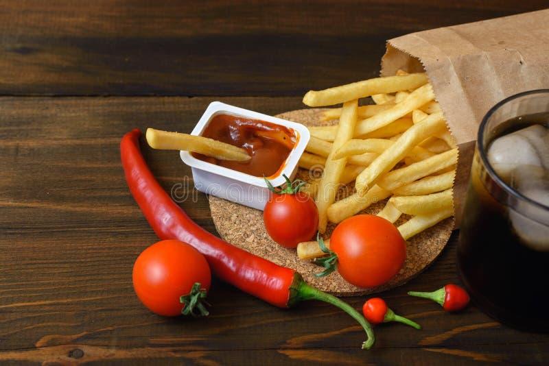 Snelle voedingsmiddelen: frieten met saus en voedselingrediënten op donkere houten lijst royalty-vrije stock fotografie