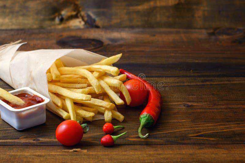 Snelle voedingsmiddelen: frieten met saus en voedselingrediënten op donkere houten lijst stock foto's