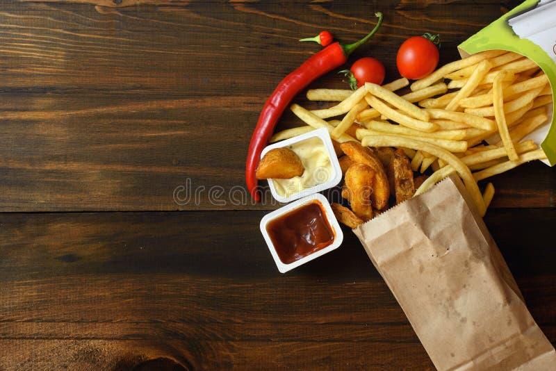 Snelle voedingsmiddelen: frieten met saus en voedselingrediënten op donkere houten lijst met exemplaar ruimte, hoogste mening stock foto