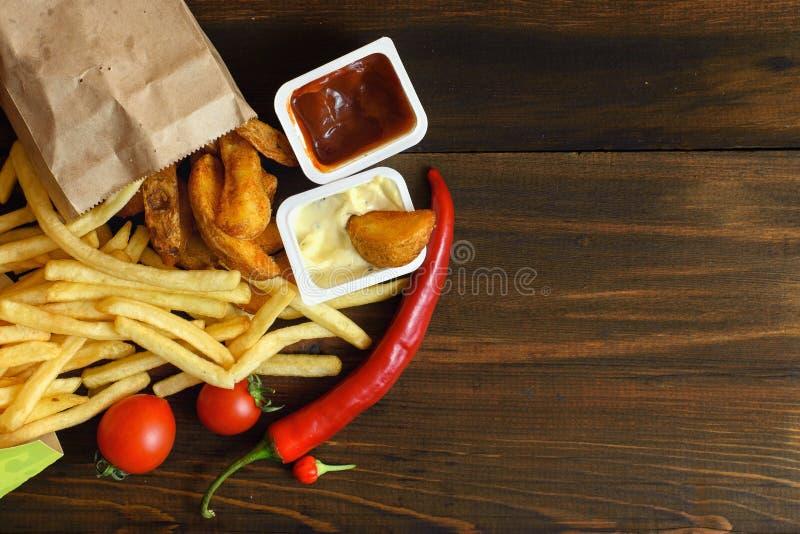 Snelle voedingsmiddelen: frieten met saus en voedselingrediënten op donkere houten lijst met exemplaar ruimte, hoogste mening royalty-vrije stock afbeeldingen