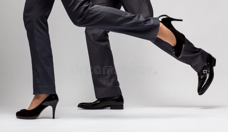 Snelle zaken: het mannelijke en vrouwelijke benen lopen stock fotografie