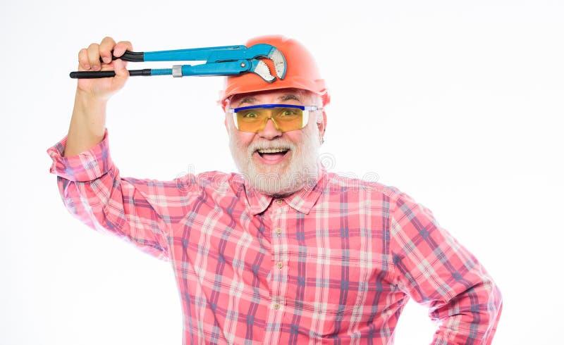 Snickare i f?rtvivlan mogen skäggig man i hardhat yrkesmässig repairman i hjälm med gasskiftnyckeln reparation och knipa arkivfoton