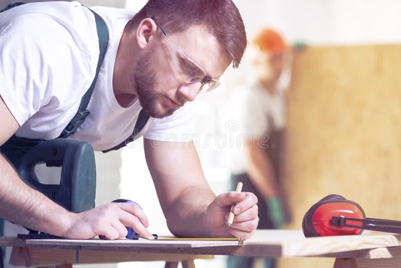 Snickare med projekt för blyertspennateckning på ett stycke av trä medan a arkivbild