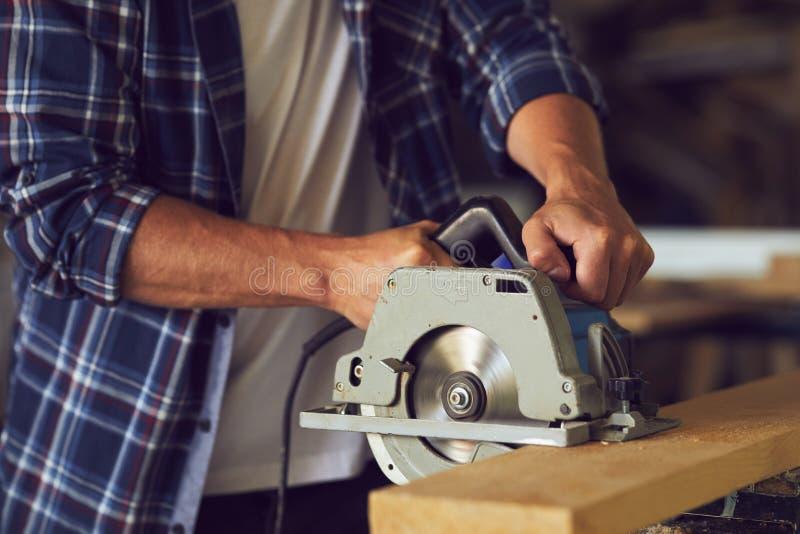Snickare som använder cirkelsågen för att klippa en träplanka arkivbild