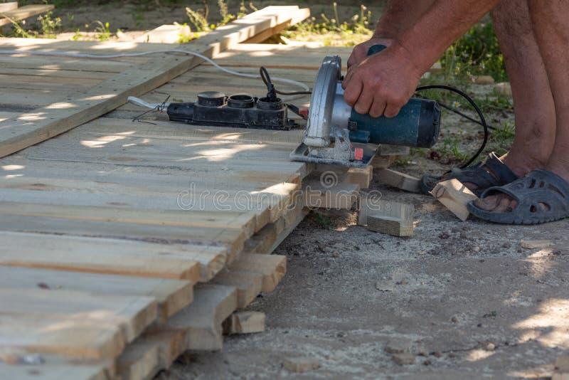 Snickare som använder cirkelsågen för att klippa träbräden fotografering för bildbyråer
