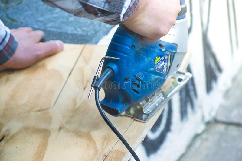Snickare som använder cirkelsågen för att klippa träbrädet arkivfoton