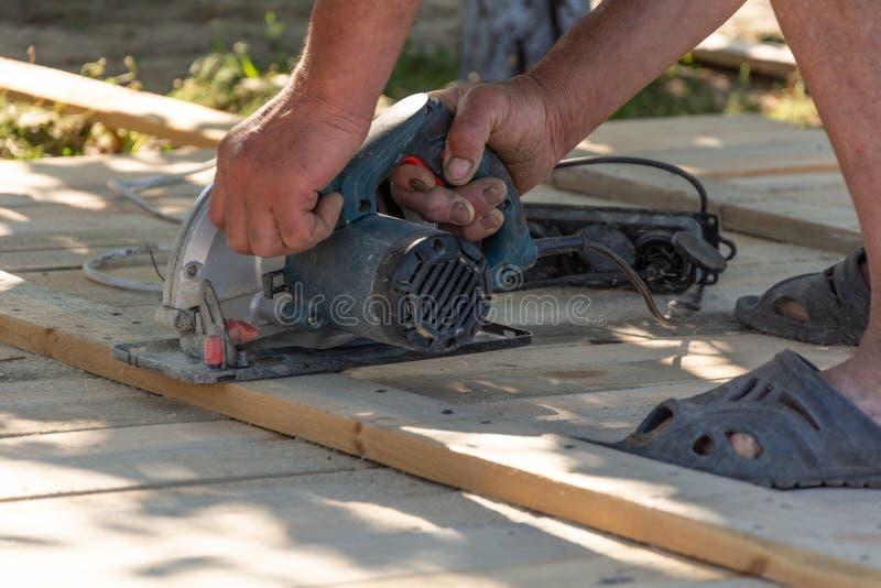 Snickare som använder en cirkelsåg för att klippa en wood brädeformwork arkivfoto