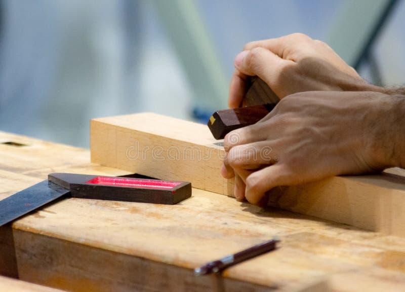 Snickare som arbetar med nivån på trä royaltyfri foto
