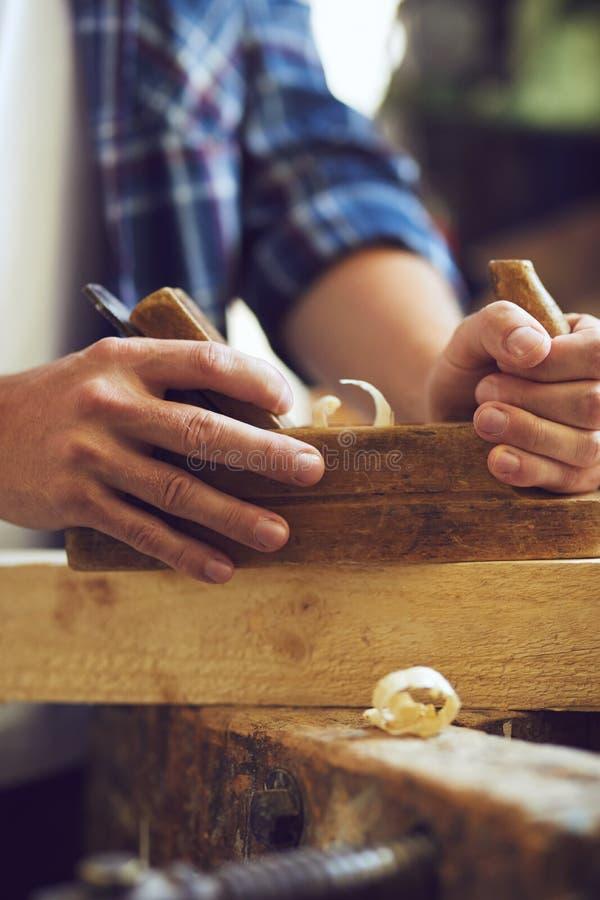 Snickare som arbetar med nivån på träplanka arkivfoto
