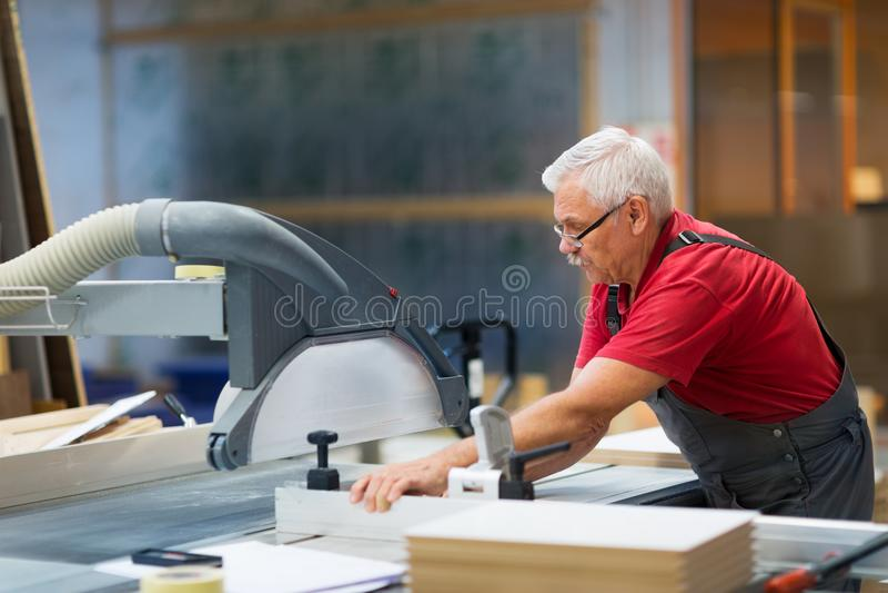 Snickare som arbetar med panelsågen på fabriken royaltyfria bilder