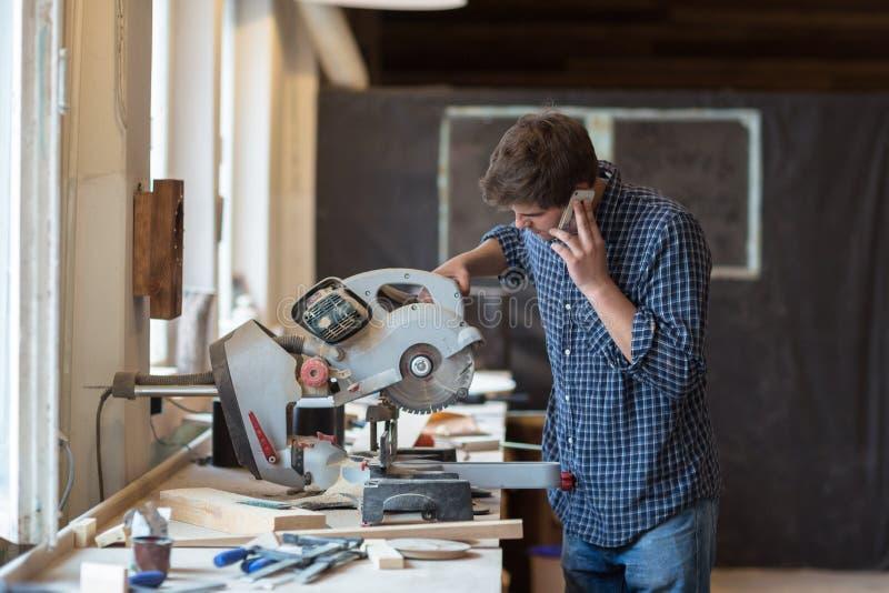 Snickare som arbetar på hans hantverk i ett dammigt seminarium arkivfoto