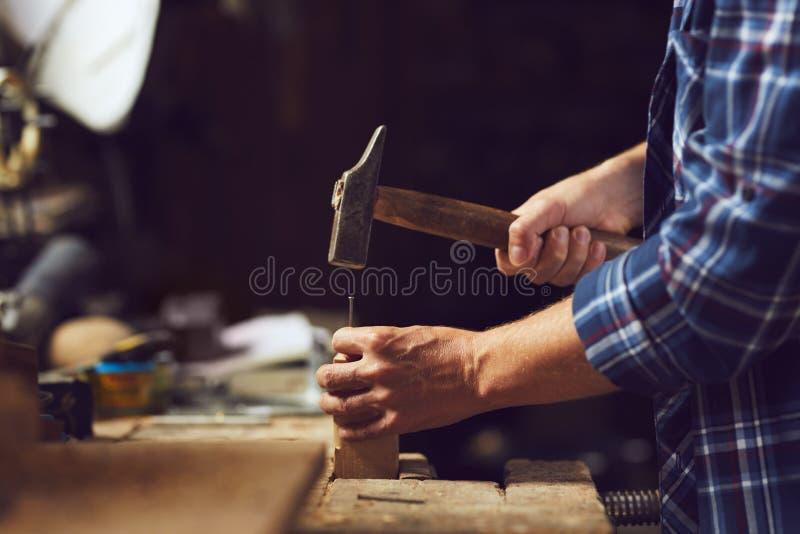 Snickare som bultar en spika in i träplanka royaltyfri foto