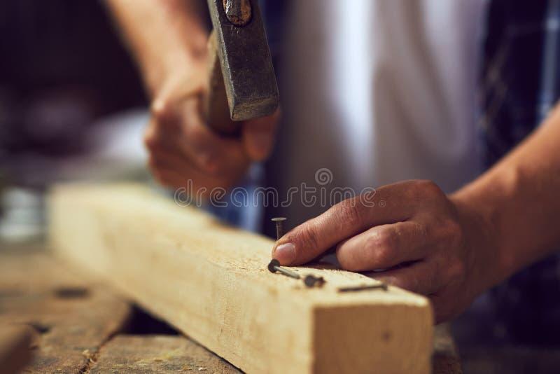 Snickare som bultar en spika in i träplanka i hans seminarium royaltyfri foto