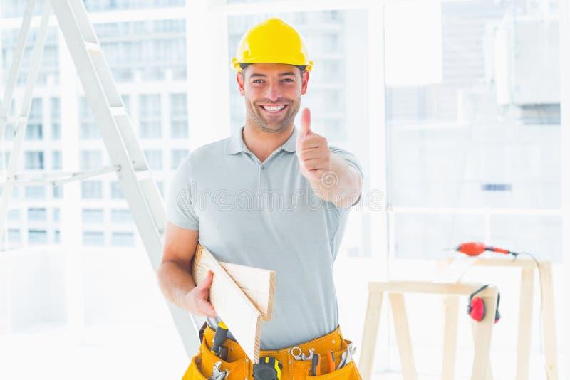 Snickare som gör en gest upp tummar på konstruktionsplatsen arkivfoto