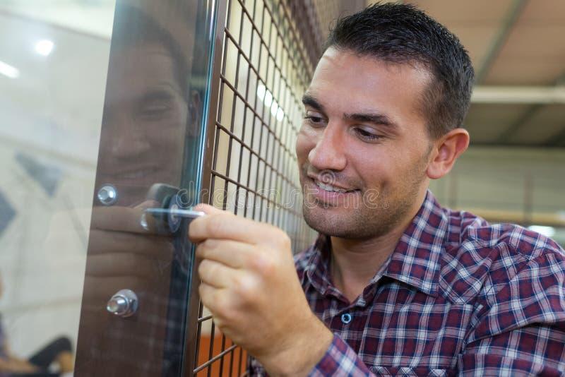 Snickare som installerar den nya dörrknoppen med låset fotografering för bildbyråer
