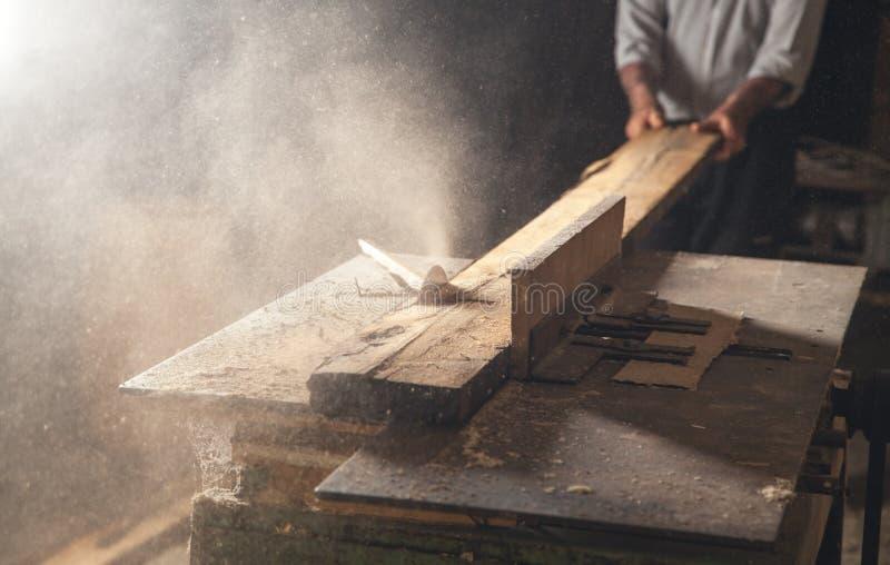 Snickare som klipper en träplanka med en snickerimaskin arkivbilder
