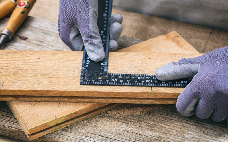 Snickare som mäter med en metallvinkel arkivbild