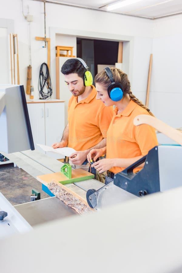Snickare som programmerar datoren - kontrollerad såg arkivfoton