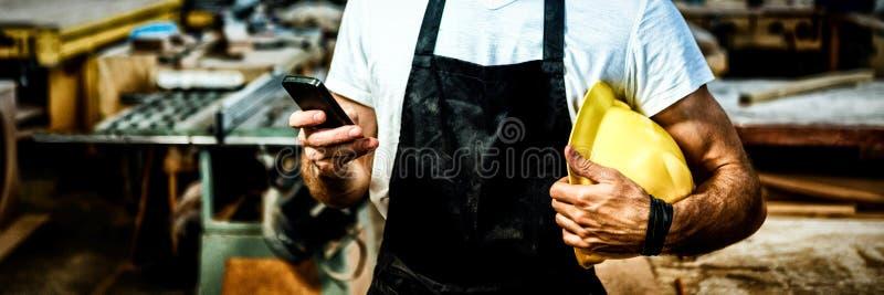 Snickare som smsar någon och rymmer hans hjälm fotografering för bildbyråer