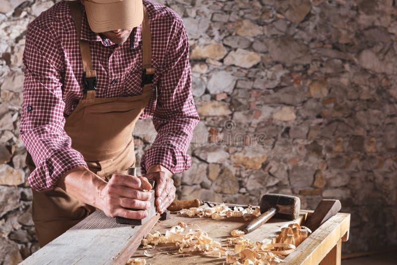 Snickare som ut slätar den långa trästrålen med hjälpmedlet royaltyfri fotografi