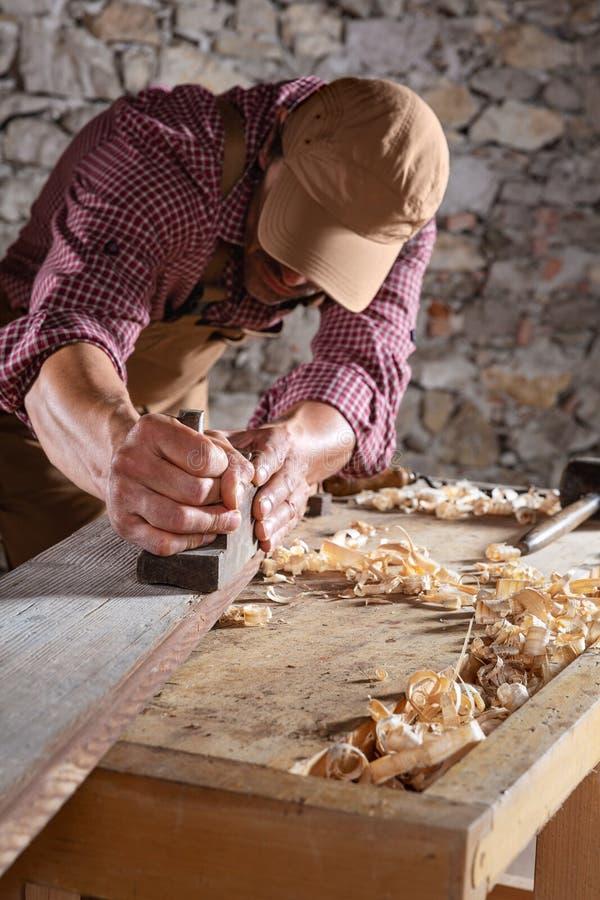 Snickare som ut slätar den långa trästrålen med hjälpmedlet arkivfoton