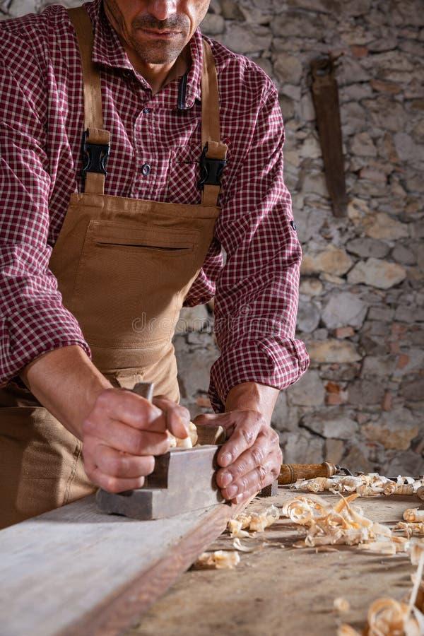 Snickare som ut slätar den långa trästrålen med hjälpmedlet royaltyfri bild