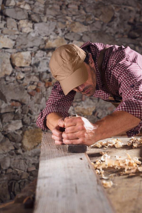 Snickare som ut slätar den långa trästrålen med hjälpmedlet royaltyfri foto