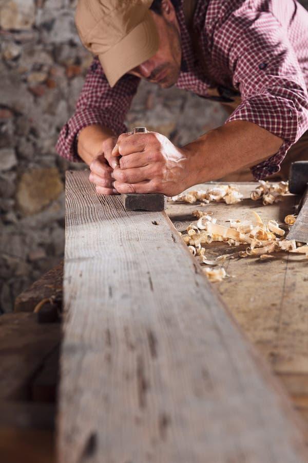 Snickare som ut slätar den långa trästrålen med hjälpmedlet royaltyfria foton