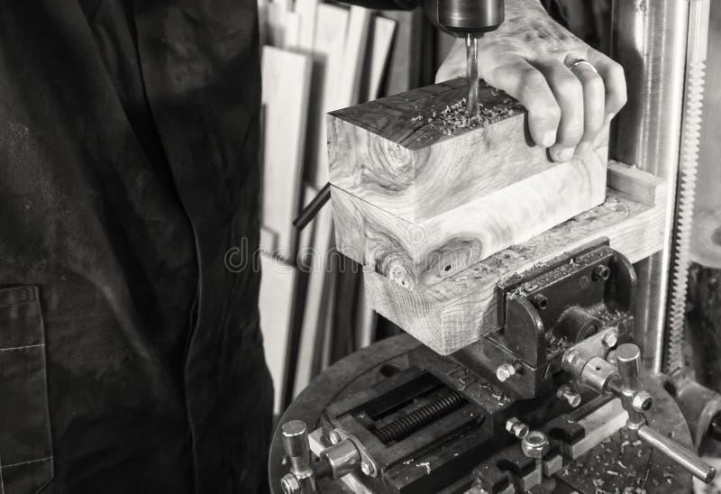 Snickarearbetsplatsman som använder en drillborrpress på trä royaltyfri bild