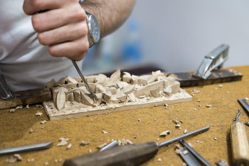 Snickarehantverkare som snider trä med hjälpmedel arkivbilder