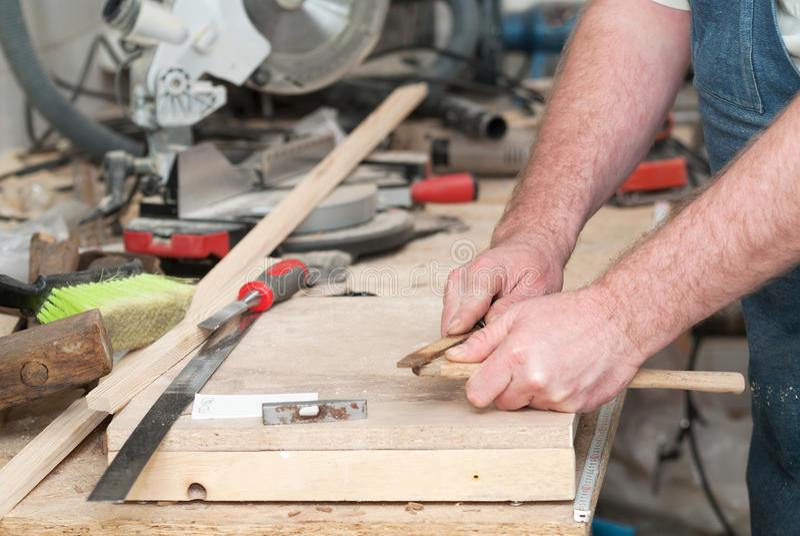 Snickarehjälpmedel på trätabellen med sågspåncirkelsågen Klippa en träplanka arkivfoto