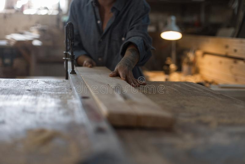 Snickarekvinnan arbetar på en såg som sågar en träprodukt royaltyfri fotografi