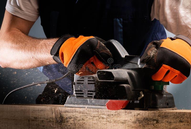 Snickaren arbetar med den elektriska hyvlaren arkivfoto