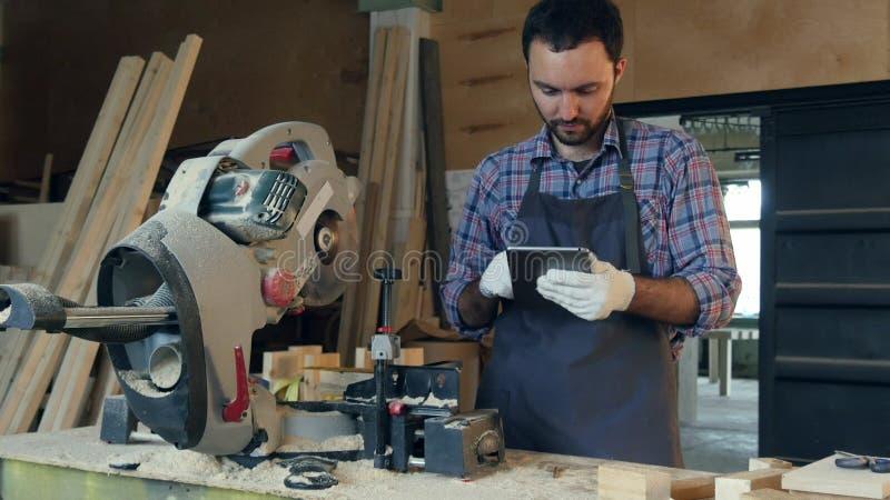 Snickaren arbetar på minnestavlan nära den elektriska sågen i seminarium royaltyfria bilder