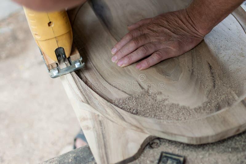 Snickaren klipper ett bräde med lövsåg royaltyfria foton