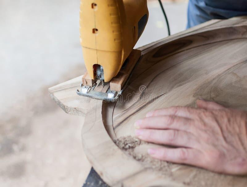 Snickaren klipper ett bräde med lövsåg royaltyfri bild