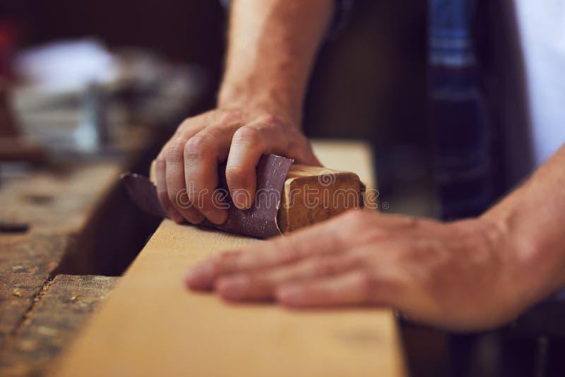 Snickaren som använder sandpapper på en träplanka i ett snickeri, shoppar royaltyfri bild