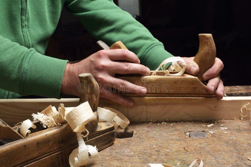 Snickaren som arbetar med nivån på trä arkivbilder