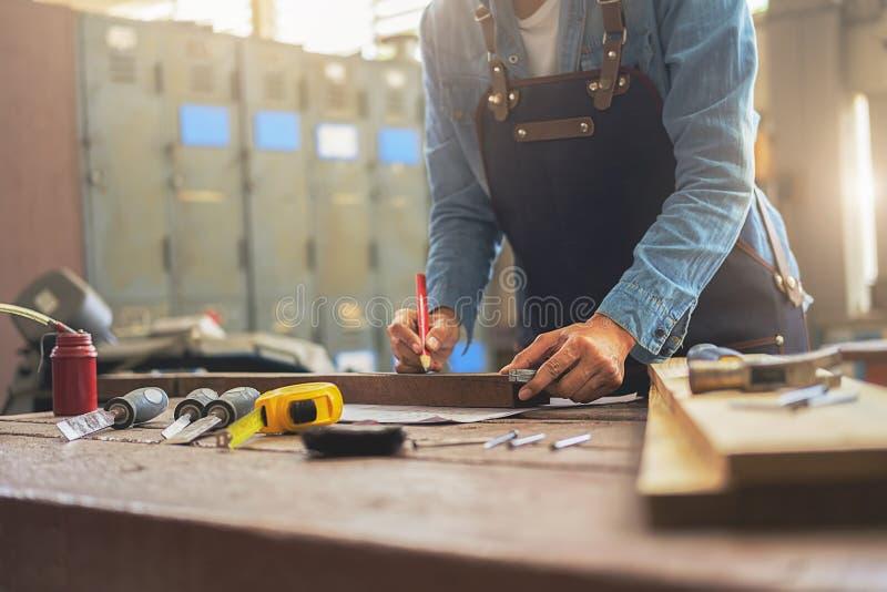 Snickaren som arbetar på snickerimaskiner i snickeri, shoppar A M. royaltyfri bild