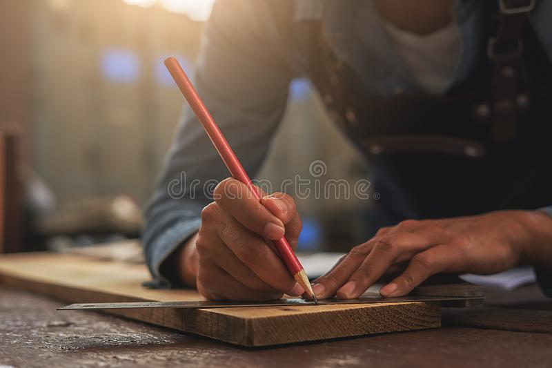 Snickaren som arbetar på snickerimaskiner i snickeri, shoppar Wom arkivfoto