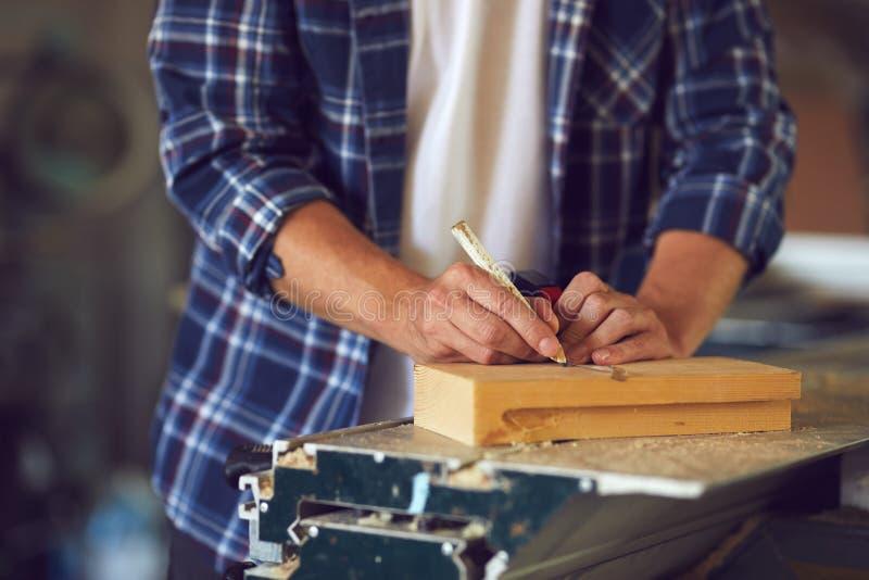 Snickaren som mäter en träplanka i ett snickeri, shoppar arkivfoton