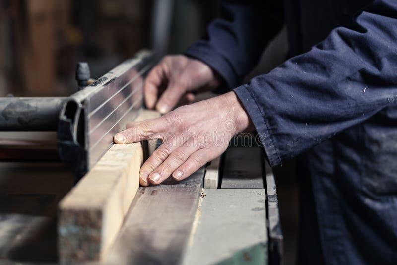 Snickares händer som klipper trä med Tablesaw royaltyfria bilder
