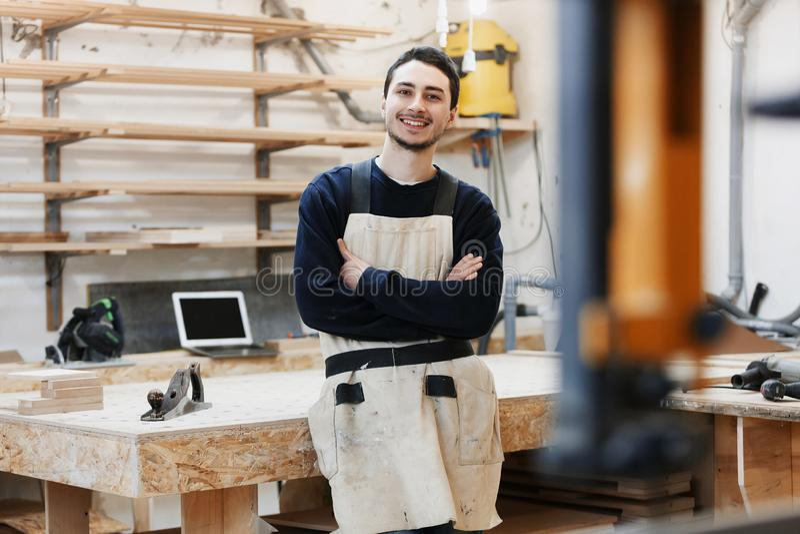 Snickares stående i arbetskläder framme av arbetsbänken Stående av att le mannen på arbete i snickareseminarium start royaltyfri bild