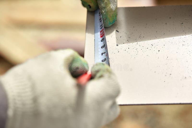 Snickeri mans handen genom att använda måttband att mäta träplankan och markera den med blyertspennan fotografering för bildbyråer